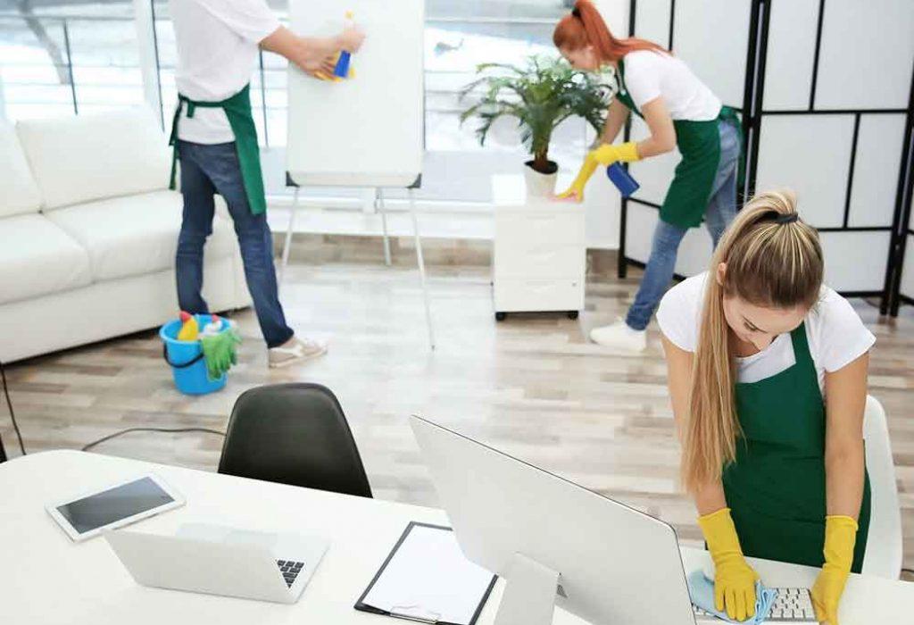 3 personnes désinfectent le mobilier d'un bureau
