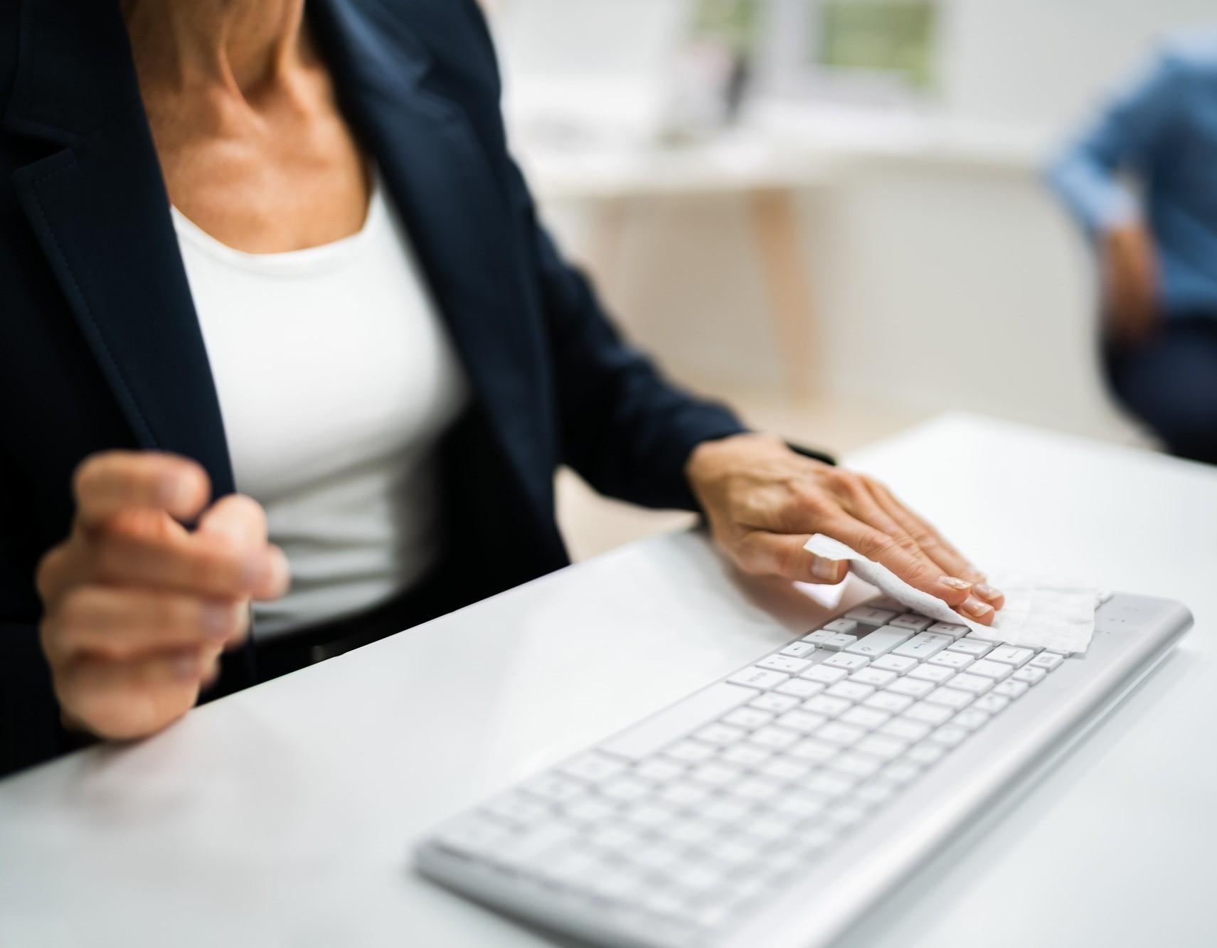 une femme nettoie son clavier d'ordinateur avec une lingette