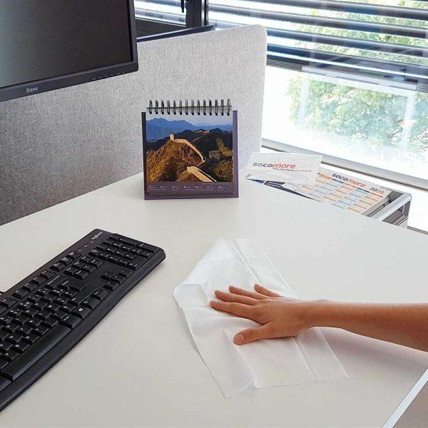 Une main nettoie avec une lingette désinfectante un bureau