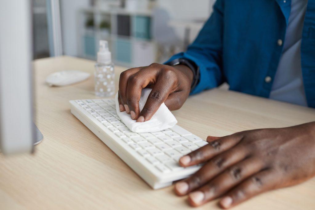 2 mains d'homme nettoie avec une lingette un clavier d'ordinateur