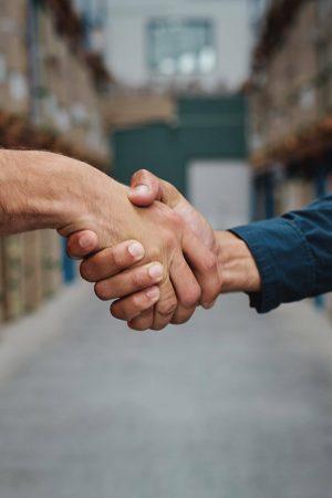 2 hommes se serrent la mains dans un entrepôt de stockage