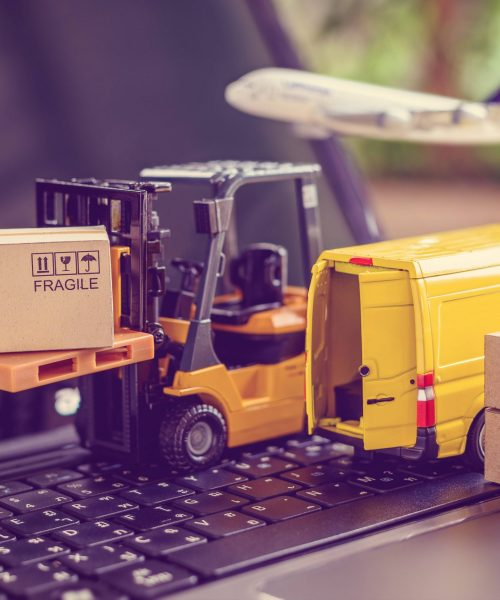 Des jouets camions, porte-charges, caisses placés sur un ordinateur portable